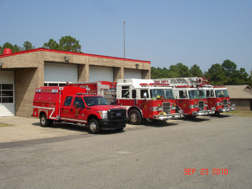 Front of Fire Station with 4 Fire Trucks Parked in Front