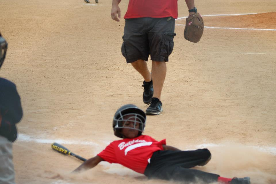 A young boy sliding into a base while playing baseball.